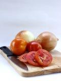 Tomates cortados y cebollas en la tabla de cortar de madera Foto de archivo