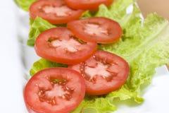 Tomates coupées en tranches sur des feuilles de laitue Photos stock