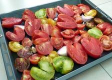 Tomates coupées en tranches sur le plateau de traitement au four Photographie stock libre de droits