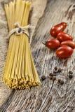 Tomates crudos de los espaguetis o del fettuccine y de cereza en una tabla de madera Estilo rústico Imágenes de archivo libres de regalías