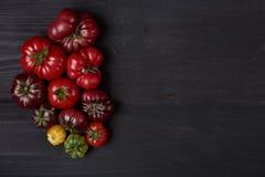 Tomates d'héritage sur le conseil noir en bois images stock
