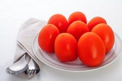 Tomates d'un plat avec la cuillère et fourchette du côté Photo stock