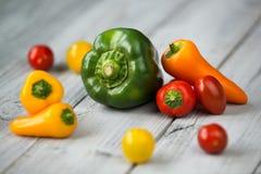 Tomates da mistura e de cereja da paprika, mini pimentas vermelhas, amarelas e alaranjadas doces e pimenta verde em um fundo de m Imagem de Stock Royalty Free