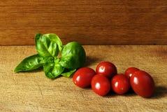 Tomates da uva e um laefe da manjericão em uma placa de madeira em um estúdio Fotos de Stock Royalty Free