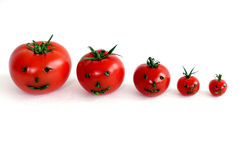 5 tomates da videira com caras do smiley em seguido no fundo branco Foto de Stock