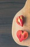 Tomates dados forma coração na placa de corte de madeira imagens de stock