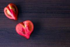 Tomates dados forma coração na tabela de madeira fotografia de stock