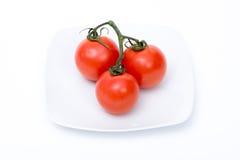 Tomates dans un plat blanc Images stock