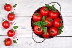 Tomates dans un pot sur la vue supérieure en bois blanche de table images libres de droits