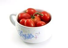Tomates dans une cuvette d'isolement sur le blanc Photos libres de droits