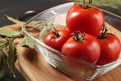 Tomates dans une cuvette en verre Photos stock