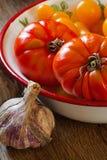 Tomates dans une cuvette et un ail Photos stock