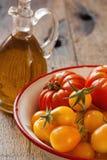 Tomates dans une cuvette et une huile d'olive Image stock