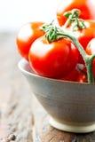 Tomates dans une cuvette sur la vieille fin en bois de verticale de table  Photos stock