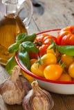 Tomates dans une cuvette, un ail, un basilic et une huile d'olive Photo libre de droits