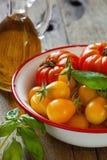 Tomates dans une cuvette, un basilic et une huile d'olive Photos stock