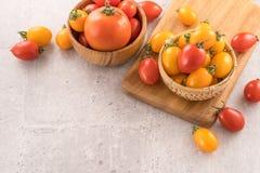 Tomates de cereja amarelos e vermelhos frescos em uma cesta em uma placa do cimento, fim acima, espaço da cópia, vista superior fotos de stock royalty free
