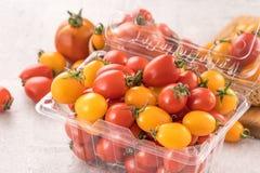 Tomates de cereja amarelos e vermelhos frescos em uma cesta em uma placa do cimento, fim acima, espaço da cópia, vista superior foto de stock royalty free