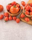 Tomates de cereja amarelos e vermelhos frescos em uma cesta em uma placa do cimento, fim acima, espaço da cópia, vista superior imagem de stock royalty free
