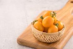 Tomates de cereja amarelos e vermelhos frescos em uma cesta em uma placa do cimento, fim acima, espaço da cópia, vista superior foto de stock