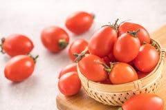 Tomates de cereja amarelos e vermelhos frescos em uma cesta em uma placa do cimento, fim acima, espaço da cópia, vista superior fotografia de stock royalty free