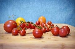 Tomates de cereja amarelos e vermelhos frescos na placa de madeira Fotos de Stock Royalty Free