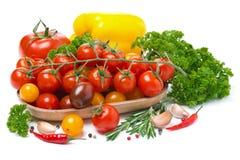 Tomates de cereja coloridos em uma bacia de madeira, pimenta, ervas Fotografia de Stock