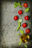 Tomates de cereja com folhas e azeite da manjericão fotografia de stock