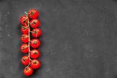 Tomates de cereja crus maduros orgânicos em um ramo longo no fundo preto da textura Espaço livre no lado direito Imagem de Stock