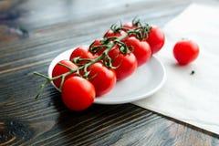 Tomates de cereja do Res no fundo de madeira Fotos de Stock Royalty Free