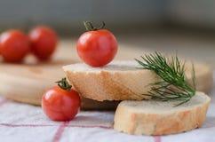 Tomates de cereja e aneto no baguette fresco cortado Foto de Stock Royalty Free
