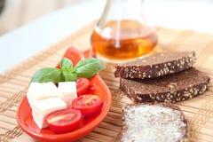 Tomates de cereja e azeitonas frescos de kalamata no brinde Fotografia de Stock Royalty Free