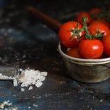Tomates de cereja em gotas e em sal da água Imagens de Stock Royalty Free