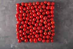 Tomates de cereja em um formulário quadrado Fundo colorido dos tomates dos tomates Conceito saudável do alimento dos tomates fres Fotografia de Stock