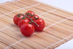 Tomates de cereja em uma esteira de bambu Fotografia de Stock Royalty Free