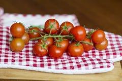 Tomates de cereja em uma toalha de cozinha vermelha Fotos de Stock Royalty Free