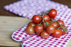 Tomates de cereja em uma toalha de cozinha vermelha Imagens de Stock Royalty Free