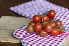 Tomates de cereja em uma toalha de cozinha vermelha Fotografia de Stock