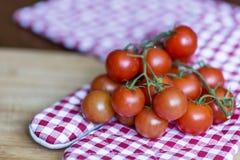 Tomates de cereja em uma toalha de cozinha vermelha Fotos de Stock