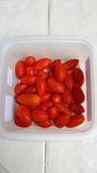 Tomates de cereja frescos em uma caixa plástica Imagens de Stock