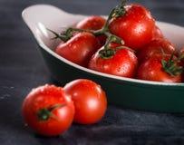 Tomates de cereja maduros em uma bacia em um fundo preto Imagem de Stock