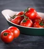 Tomates de cereja maduros em uma bacia em um fundo preto Fotos de Stock Royalty Free