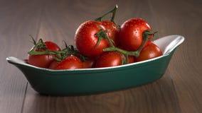 Tomates de cereja maduros em uma bacia em uma tabela de madeira Fotografia de Stock