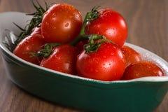 Tomates de cereja maduros em uma bacia em uma tabela de madeira Imagem de Stock Royalty Free