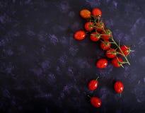 Tomates de cereja maduros frescos em um fundo escuro Vista superior Imagem de Stock
