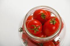 Tomates de cereja no frasco de vidro sobre o branco Fotos de Stock Royalty Free