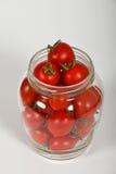 Tomates de cereja no frasco de vidro sobre o branco Fotografia de Stock Royalty Free