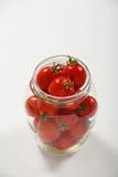 Tomates de cereja no frasco de vidro sobre o branco Imagem de Stock Royalty Free