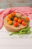 Tomates de cereja orgânicos com alecrins na tabela de madeira rústica Imagem de Stock