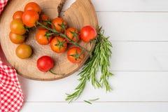 Tomates de cereja orgânicos com alecrins na tabela de madeira rústica Fotos de Stock